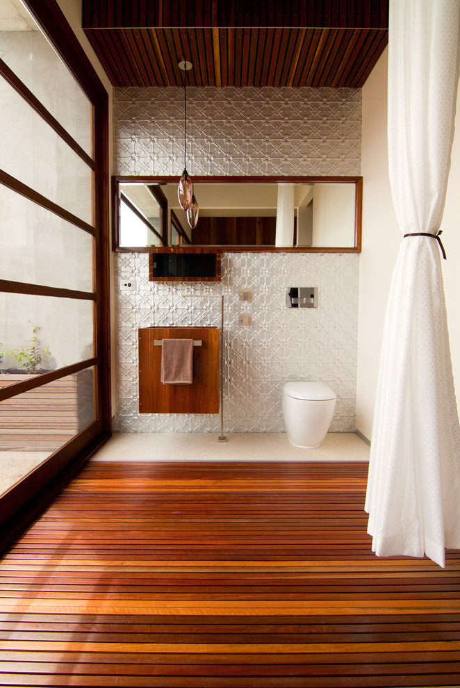 Trendy gray tile medium tone wood floor powder room photo in Other with white walls