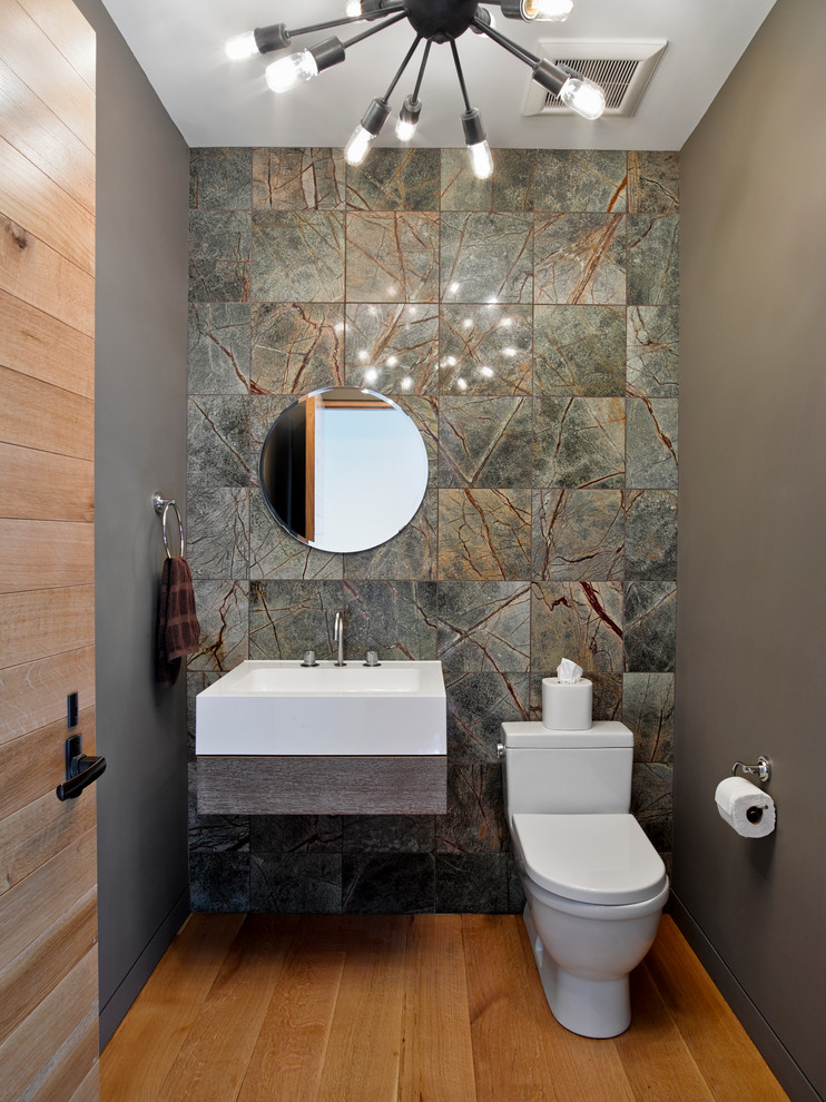 Example of a trendy marble tile and gray tile medium tone wood floor powder room design in New York with a wall-mount sink, a one-piece toilet and gray walls