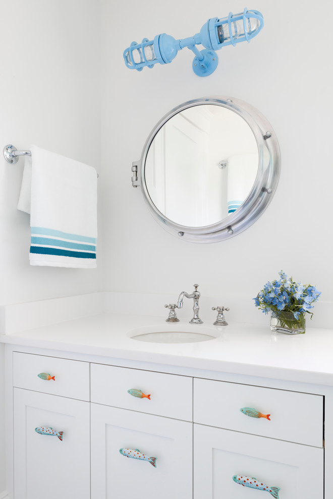 Powder room - coastal powder room idea in New York with an undermount sink, shaker cabinets, white cabinets and white countertops