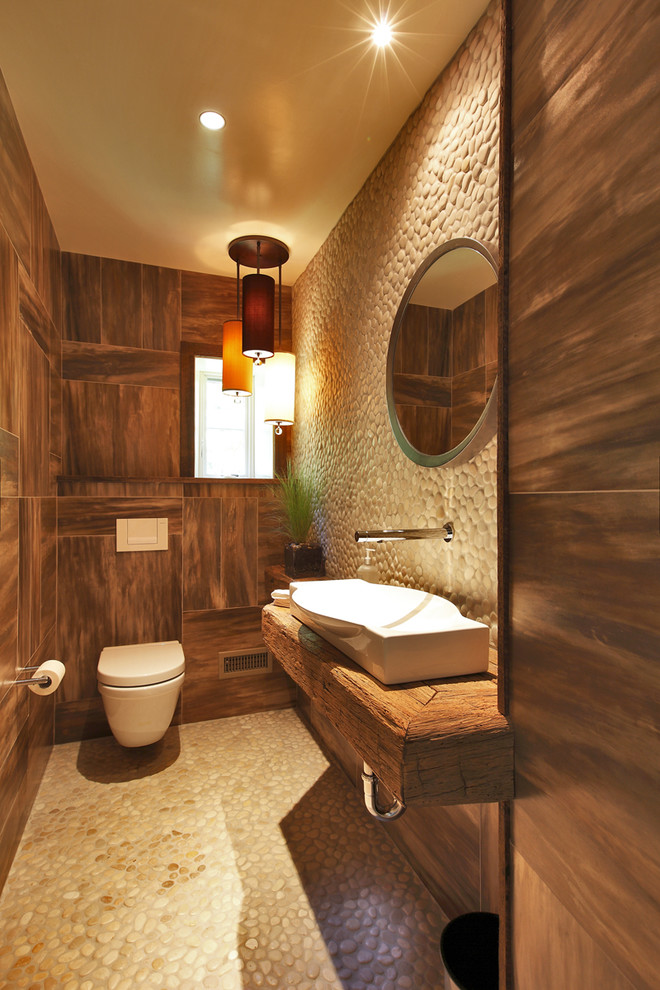 Inspiration for a small rustic beige tile and pebble tile powder room remodel in New York with wood countertops, a wall-mount toilet, a trough sink and brown countertops
