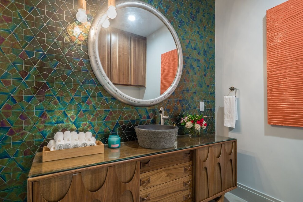 Powder room - transitional multicolored tile powder room idea in Dallas with furniture-like cabinets, medium tone wood cabinets, white walls, a vessel sink and glass countertops