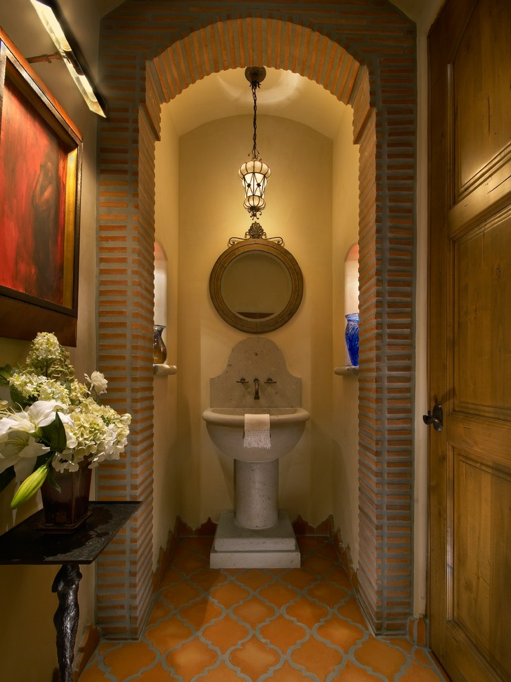 Example of a large tuscan orange tile and terra-cotta tile terra-cotta tile powder room design in Phoenix with a pedestal sink and beige walls