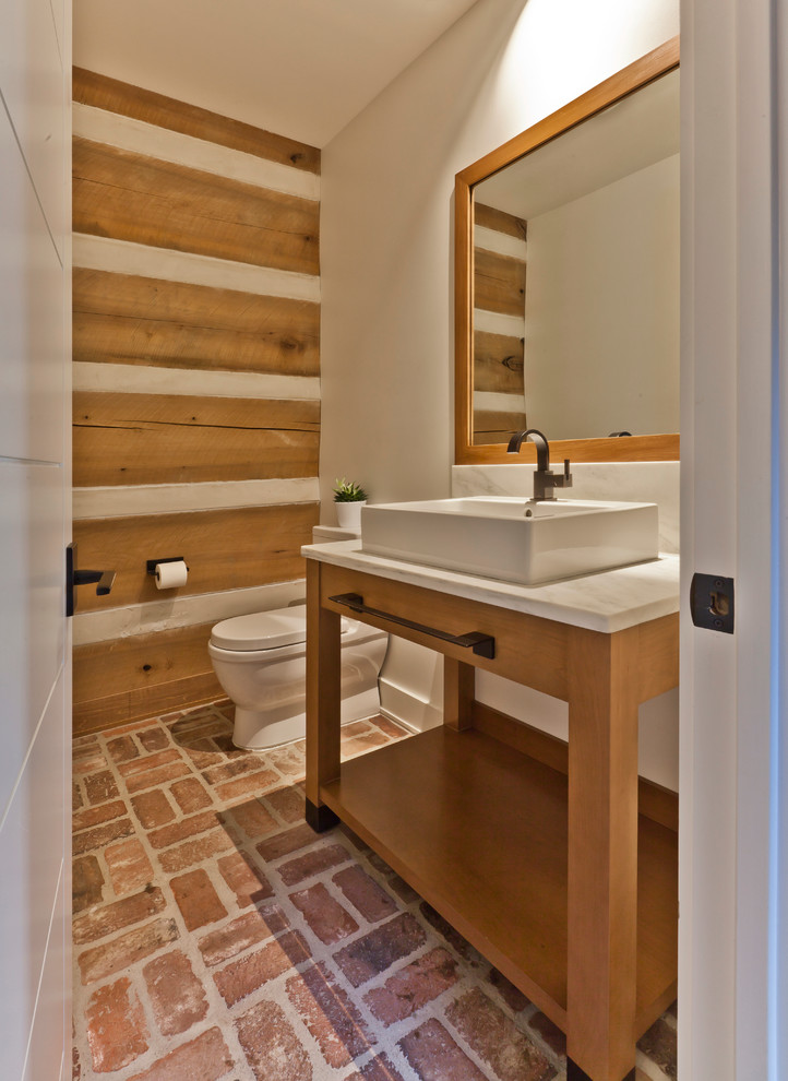 Mid-sized danish brick floor powder room photo in Indianapolis with furniture-like cabinets, medium tone wood cabinets, a one-piece toilet, white walls, a vessel sink and marble countertops