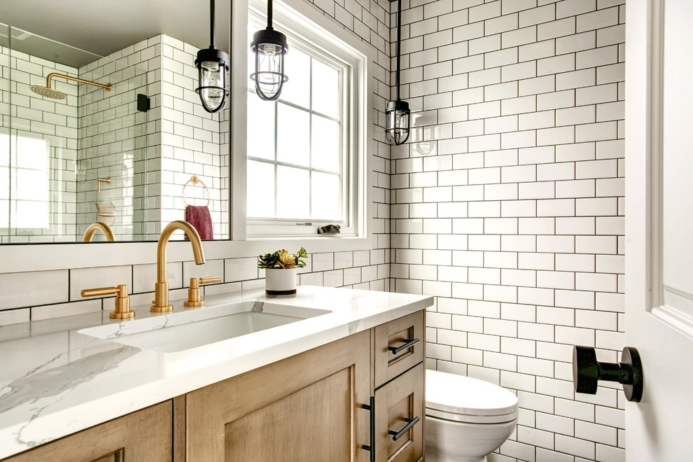 Example of a mid-sized transitional white tile and subway tile powder room design in Seattle with shaker cabinets, medium tone wood cabinets, white walls, a two-piece toilet, an undermount sink, quartzite countertops and white countertops