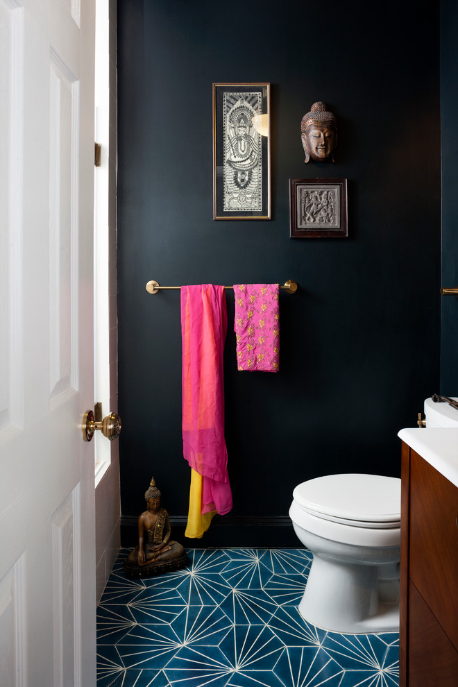 Powder room - mid-sized eclectic blue tile concrete floor powder room idea in DC Metro with a console sink, dark wood cabinets, a one-piece toilet and black walls