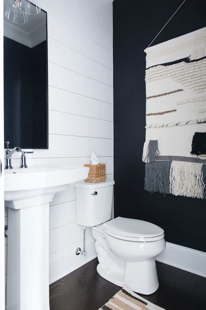 Example of a farmhouse dark wood floor and brown floor powder room design in Chicago with a two-piece toilet, black walls and a pedestal sink