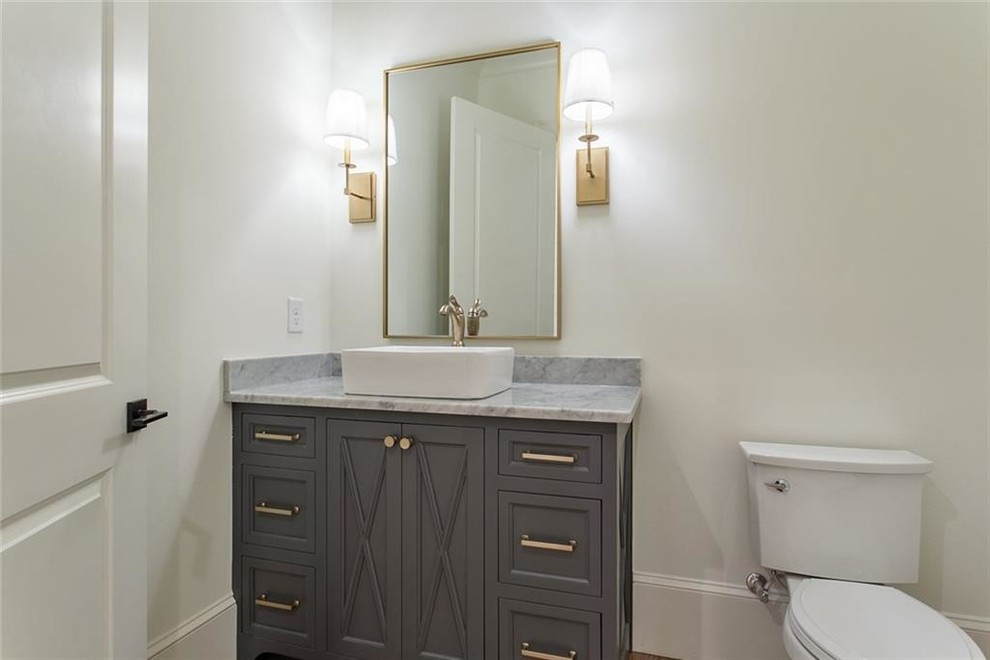 Inspiration for a mid-sized transitional light wood floor and gray floor powder room remodel in Atlanta with recessed-panel cabinets, gray cabinets, a two-piece toilet, white walls, a vessel sink, marble countertops and gray countertops
