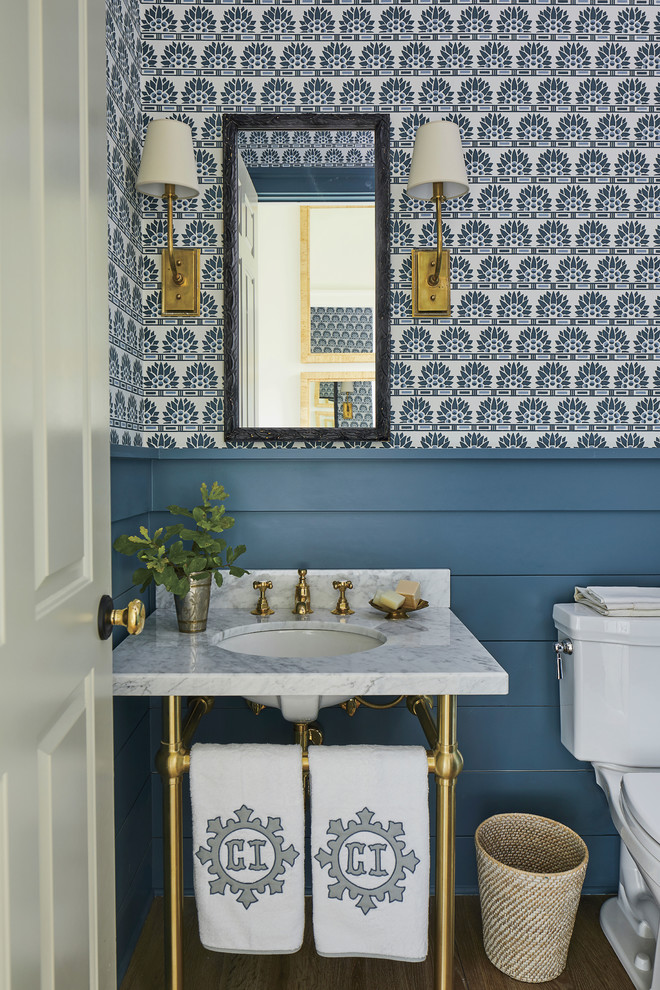 Powder room - coastal dark wood floor powder room idea in Jacksonville with multicolored walls, a console sink, marble countertops and white countertops