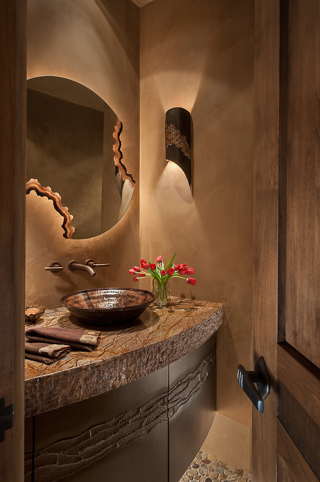 Powder room - mid-sized southwestern pebble tile floor powder room idea in Phoenix with a vessel sink, furniture-like cabinets, granite countertops, beige walls and dark wood cabinets