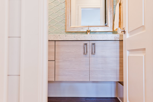 Example of a mid-sized coastal blue tile and glass tile powder room design in Jacksonville with flat-panel cabinets, light wood cabinets, an integrated sink and terrazzo countertops