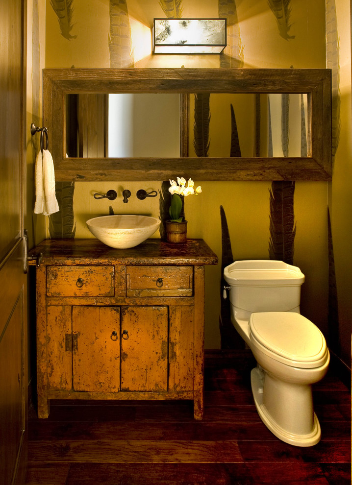 Powder room - mid-sized rustic dark wood floor powder room idea in Phoenix with a vessel sink, furniture-like cabinets, orange cabinets, wood countertops, a two-piece toilet and brown countertops