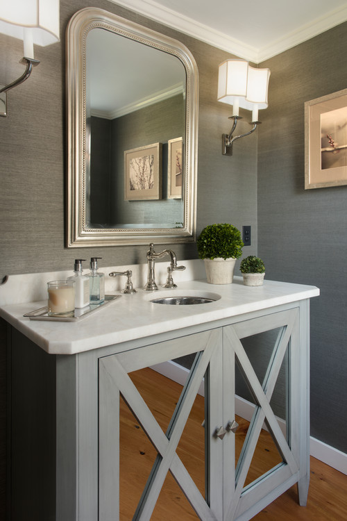 Bathroom interior design with a gray furniture vanity with mullion cabinet doors and mirror inserts.