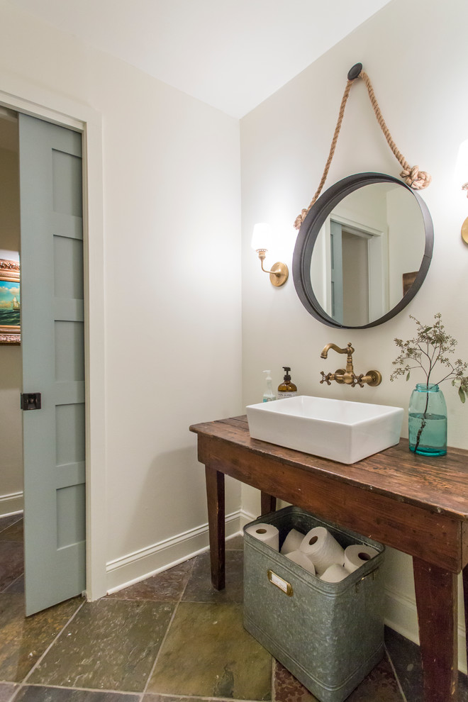 Inspiration for a farmhouse powder room remodel in Atlanta with a vessel sink, furniture-like cabinets, dark wood cabinets, wood countertops, white walls and brown countertops