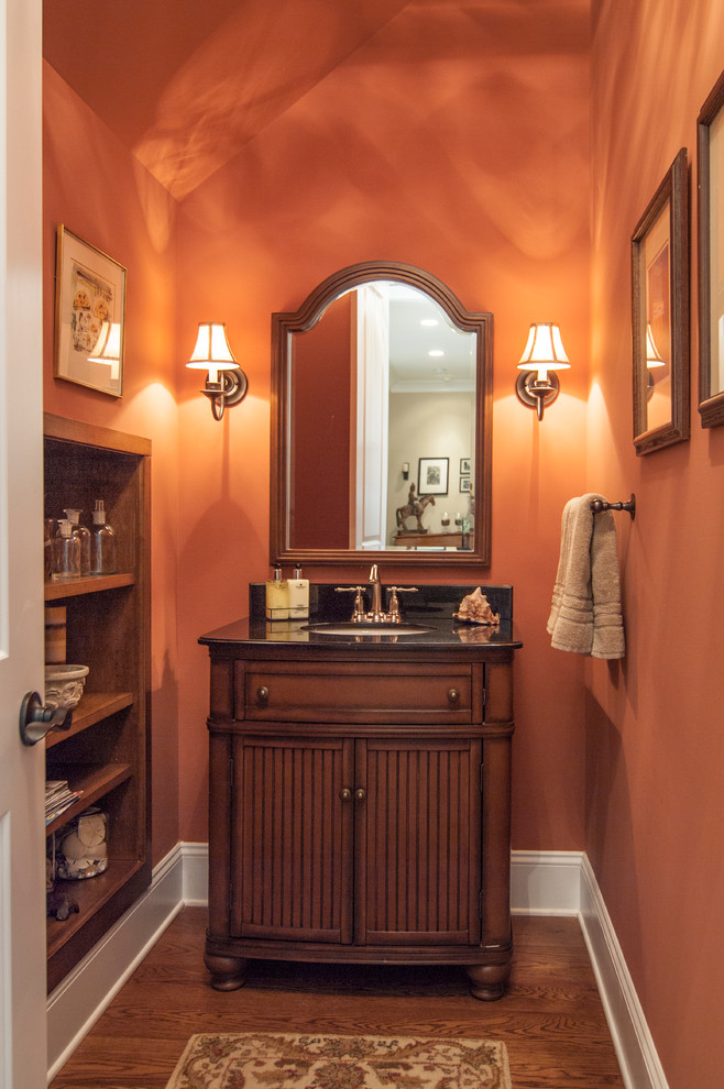 Example of a classic powder room design in Charlotte with an undermount sink, recessed-panel cabinets and dark wood cabinets