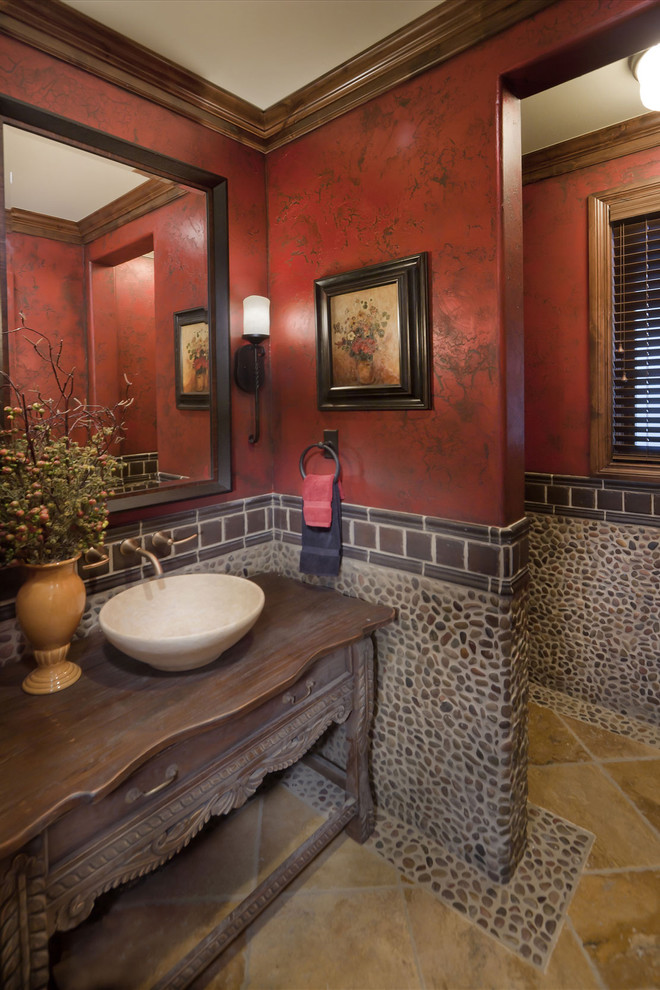 Inspiration for a mediterranean pebble tile powder room remodel in Denver with a vessel sink and red walls