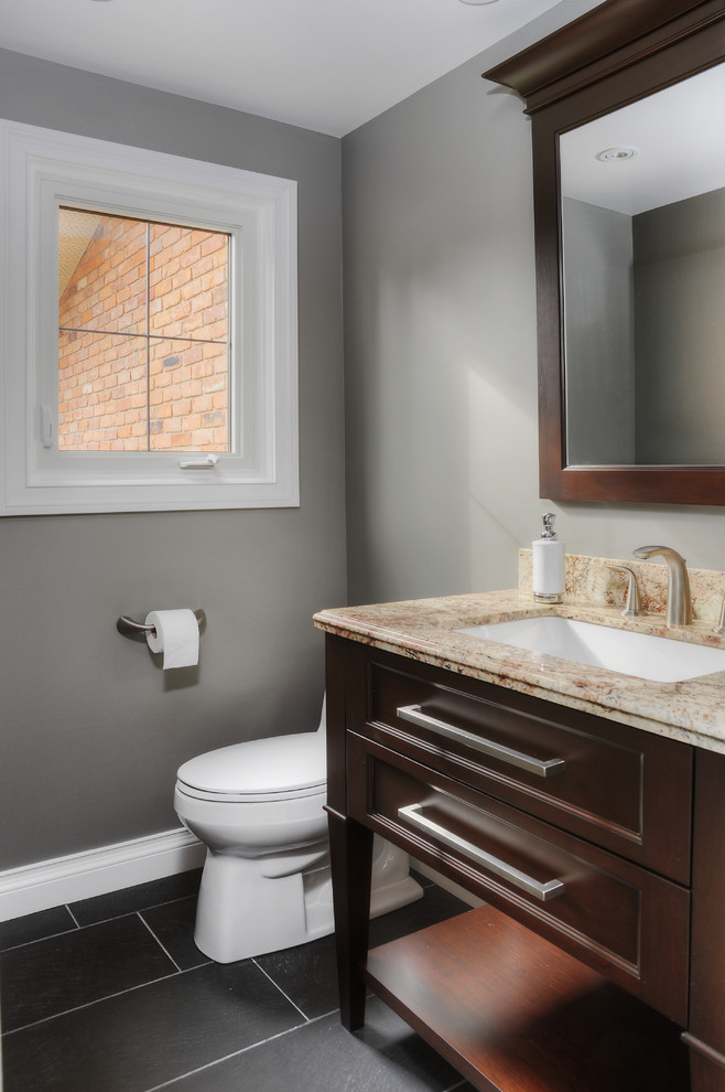 Powder room - mid-sized transitional slate floor powder room idea in Toronto with an undermount sink, recessed-panel cabinets, granite countertops, gray walls and dark wood cabinets