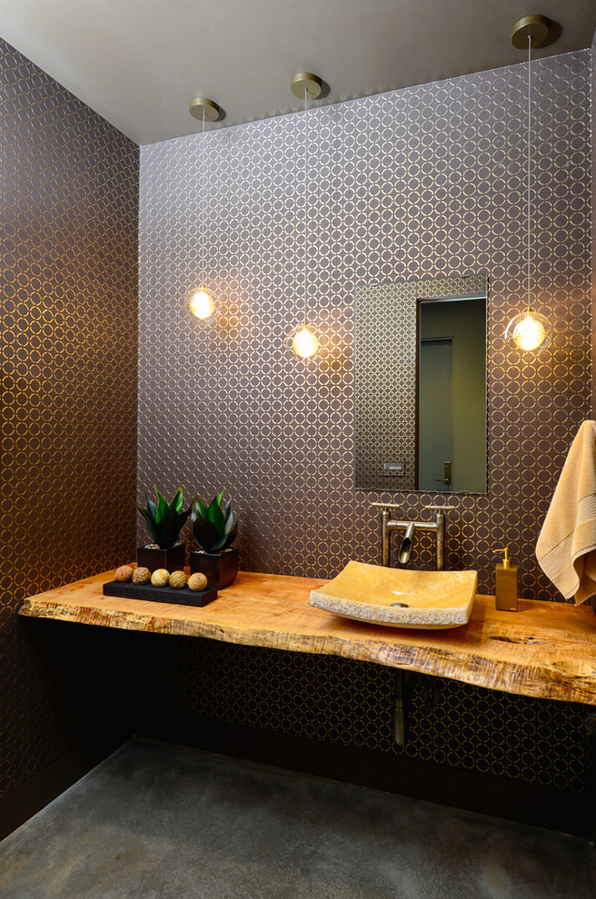 Powder room - mid-sized contemporary concrete floor powder room idea in Other with a vessel sink, wood countertops, multicolored walls and brown countertops