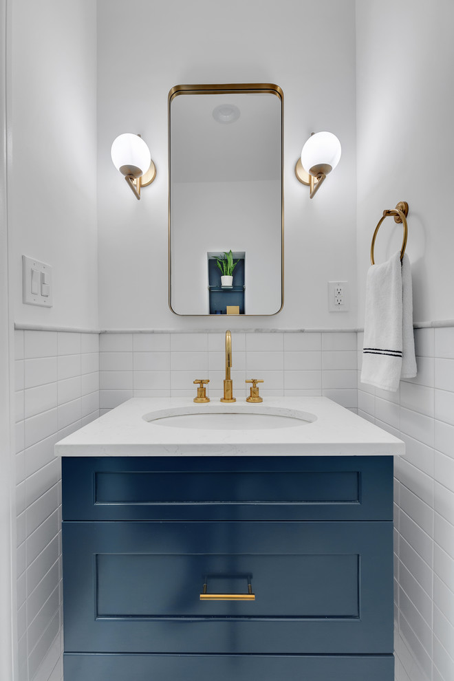 Transitional white tile powder room photo in New York with shaker cabinets, blue cabinets, white walls, an undermount sink and white countertops