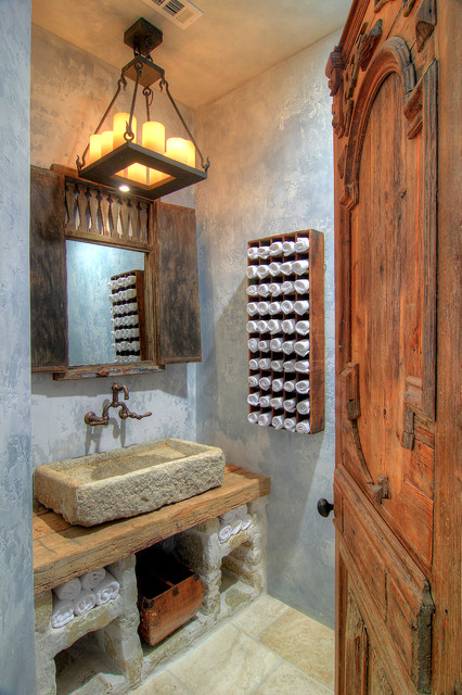 Inspiration for a mediterranean powder room remodel in Houston with a vessel sink, wood countertops, gray walls and brown countertops