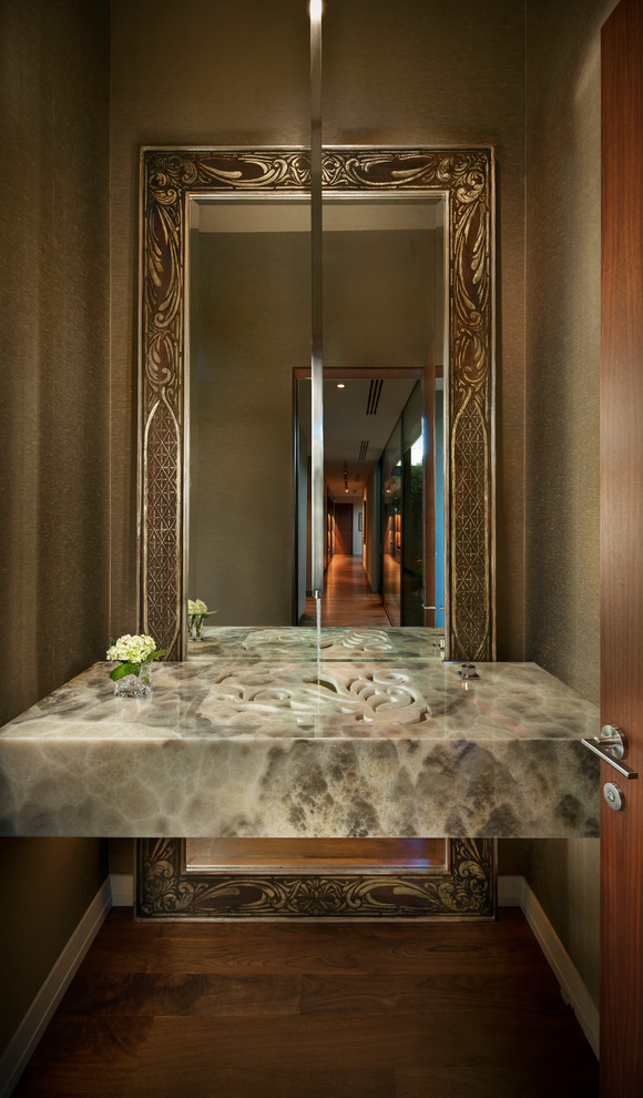 Powder room - contemporary dark wood floor powder room idea in Phoenix with an integrated sink, brown walls and gray countertops