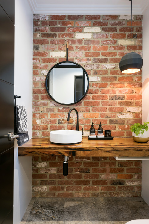 white basin in industrial powder room with brick splashback