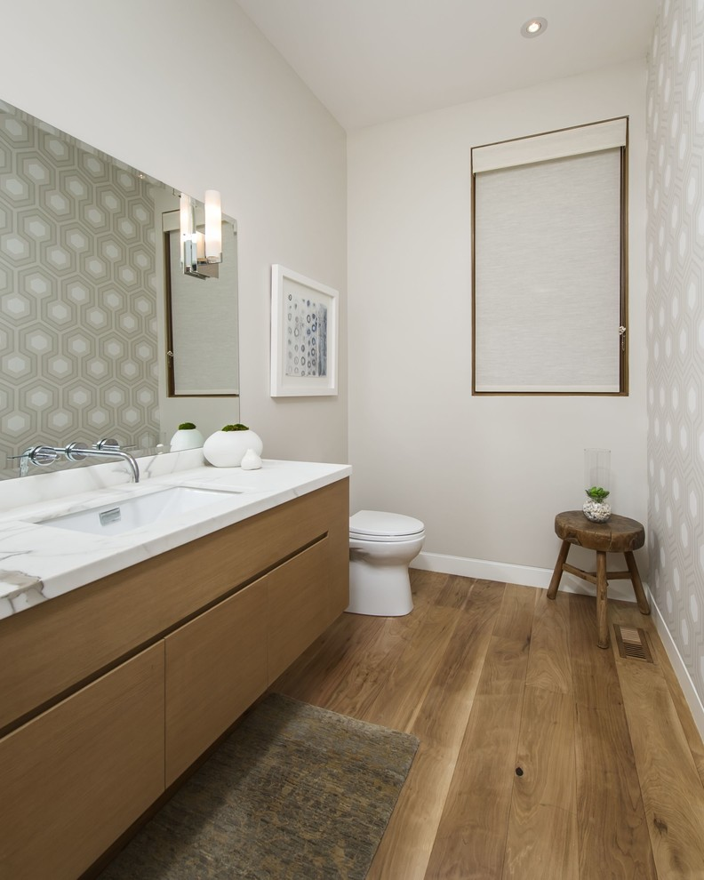 Example of a large trendy medium tone wood floor powder room design in Los Angeles with an undermount sink, flat-panel cabinets, medium tone wood cabinets, marble countertops, a one-piece toilet, beige walls and white countertops