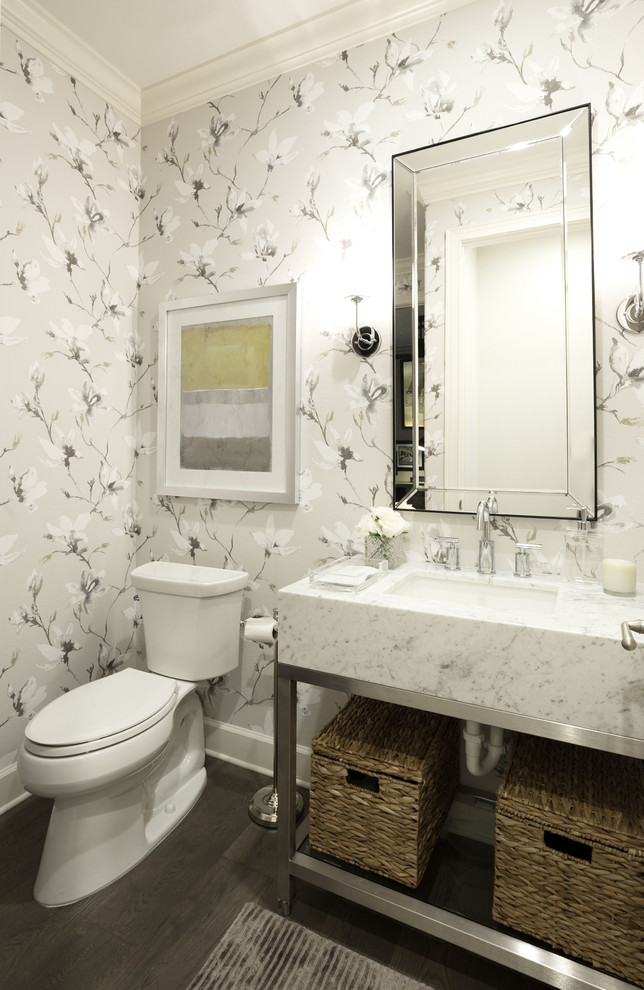Powder room - mid-sized transitional brown floor and dark wood floor powder room idea in Orlando with open cabinets, a two-piece toilet, gray walls, an undermount sink, marble countertops and white countertops