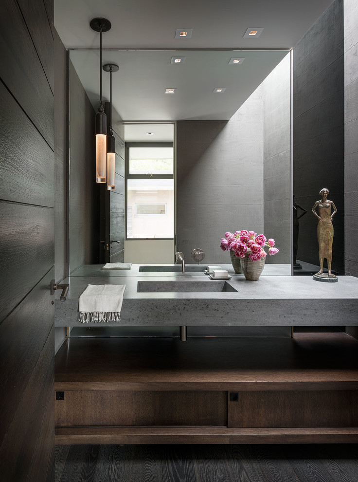 Mid-century modern dark wood floor and brown floor powder room photo in Orange County with flat-panel cabinets, dark wood cabinets, gray walls, an integrated sink and gray countertops