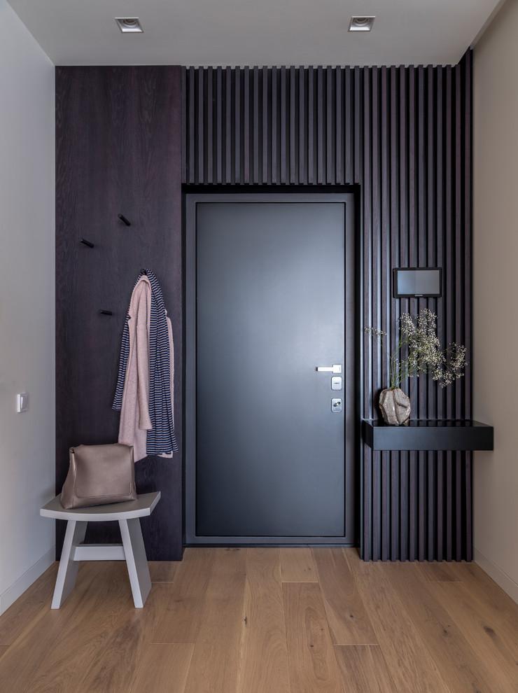 На фото: входные двери в современном стиле с черными стенами, паркетным полом среднего тона, одностворчатой входной дверью, черной входной дверью и коричневым полом