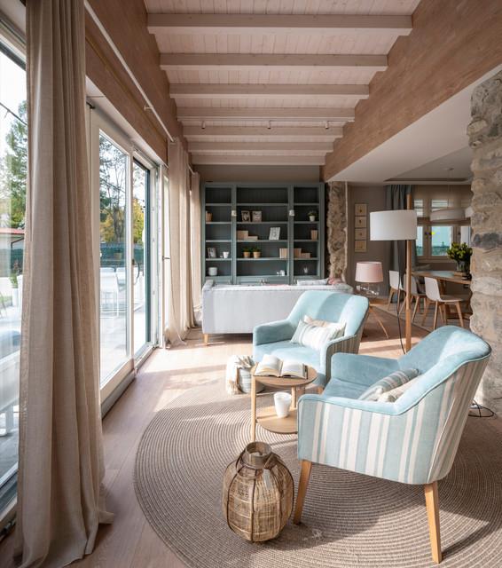 Foto de sala de estar con biblioteca abierta, escandinava, grande, sin chimenea y televisor, con paredes beige, suelo laminado y suelo marrón
