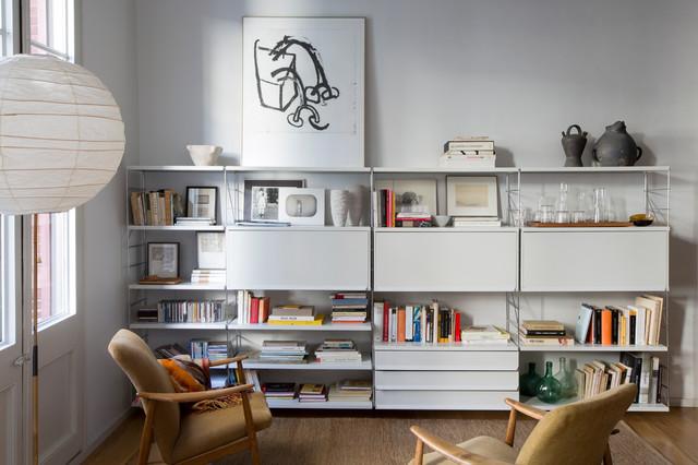 Foto de sala de estar con biblioteca cerrada, escandinava, de tamaño medio, sin chimenea y televisor, con paredes blancas y suelo de madera en tonos medios
