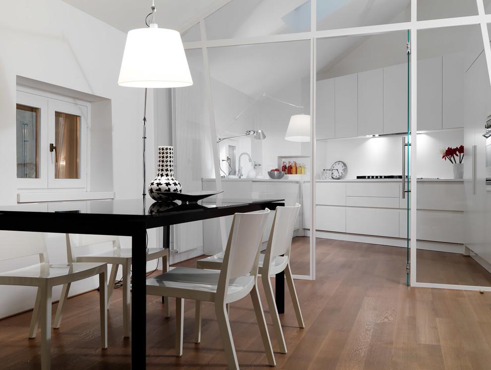 Foto di una sala da pranzo aperta verso la cucina contemporanea con pareti bianche e parquet chiaro