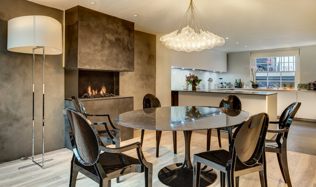 Photo of a contemporary kitchen/dining room in London with grey walls, a ribbon fireplace and a concrete fireplace surround.