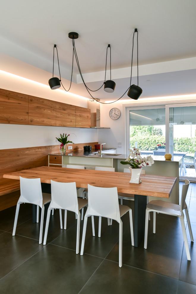 Ispirazione per una sala da pranzo aperta verso la cucina design di medie dimensioni con pareti bianche, pavimento con piastrelle in ceramica, nessun camino e pavimento nero