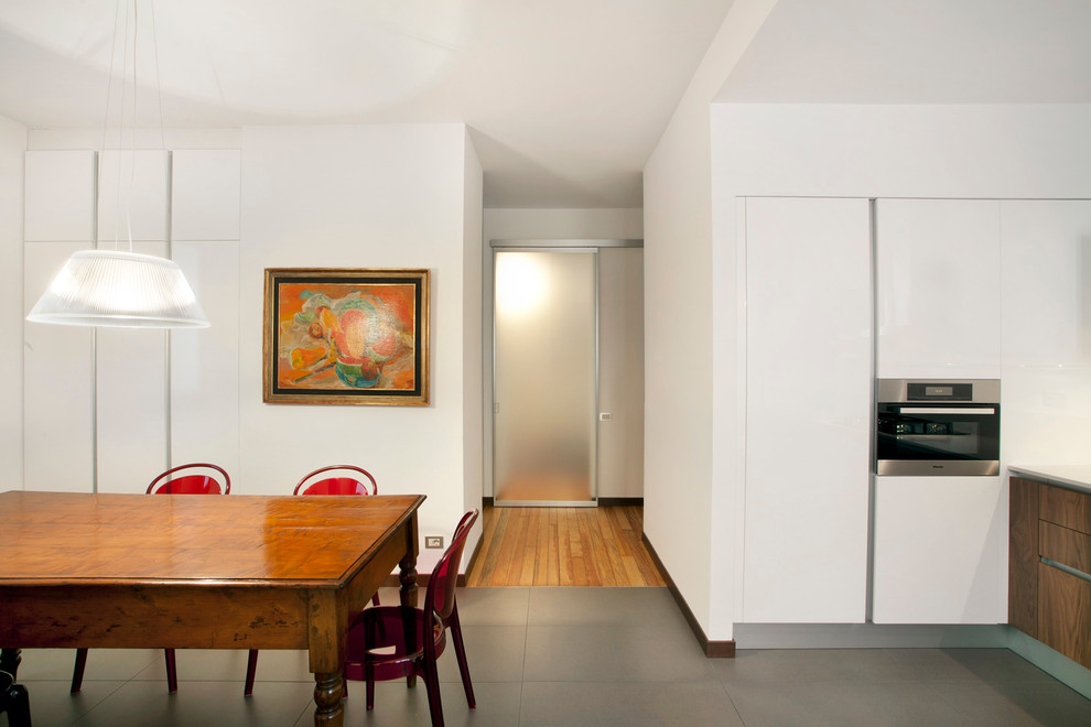 Example of a minimalist kitchen/dining room combo design in Milan with white walls and no fireplace