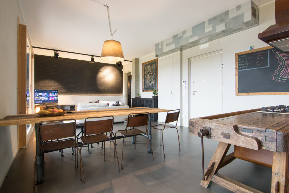 Mid-sized urban concrete floor and gray floor great room photo in Florence with gray walls