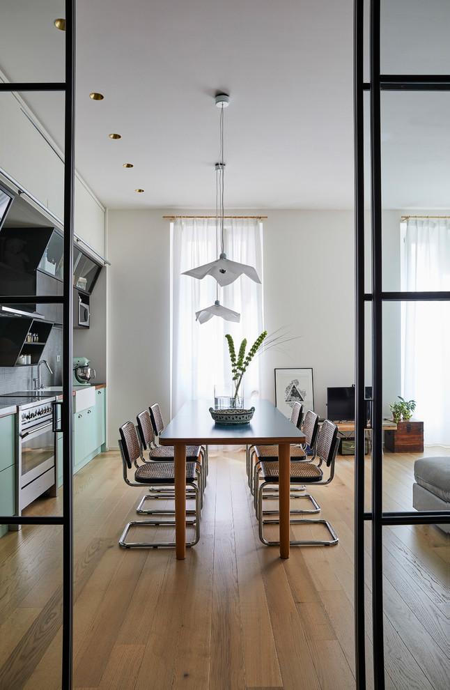 Foto di una sala da pranzo aperta verso il soggiorno minimal di medie dimensioni con pareti bianche, parquet chiaro e pavimento beige