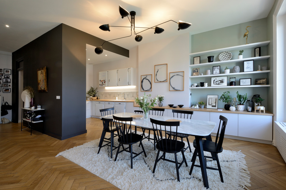 Danish medium tone wood floor and brown floor great room photo in Lyon with multicolored walls and no fireplace