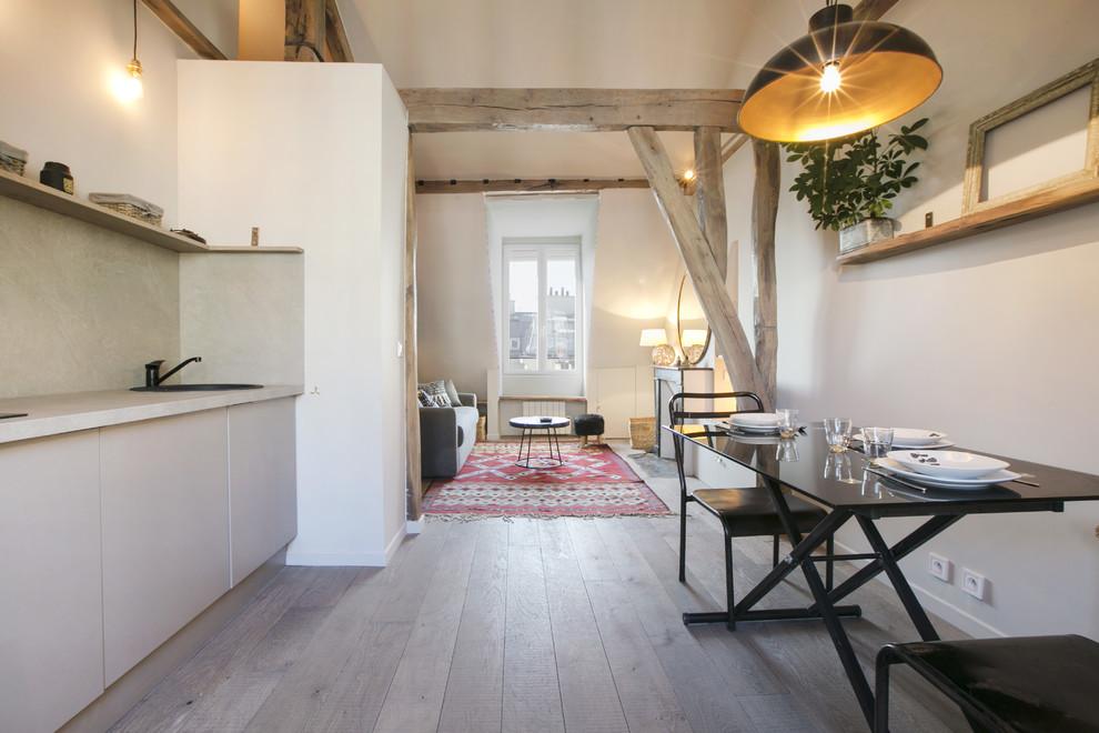 Cette photo montre une salle à manger ouverte sur la cuisine tendance de taille moyenne avec un mur blanc et un sol en bois brun.