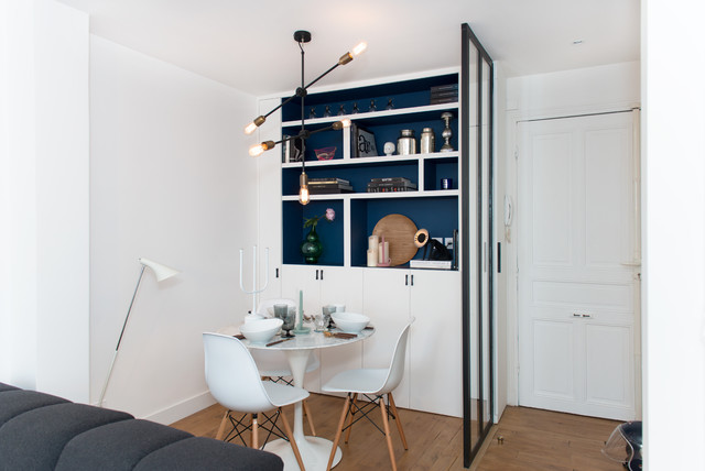 Great room - small contemporary medium tone wood floor great room idea in Paris with white walls and no fireplace