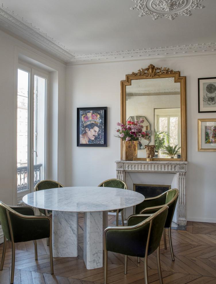 Cette image montre une salle à manger bohème fermée avec un mur blanc, un sol en bois brun, une cheminée standard et un sol marron.
