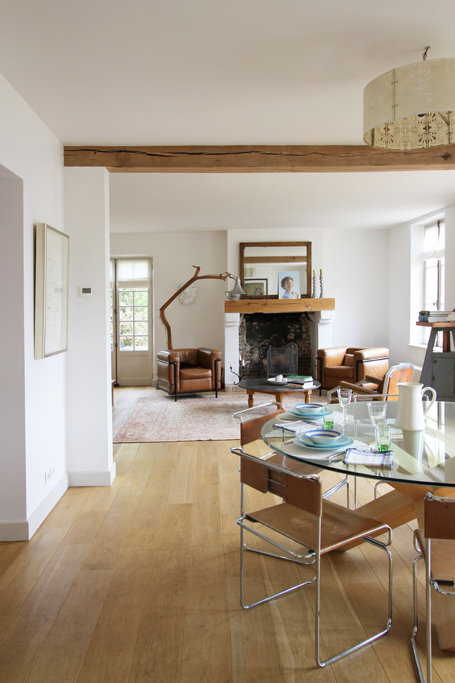 Example of a mid-sized 1950s medium tone wood floor great room design in Paris with white walls and a standard fireplace