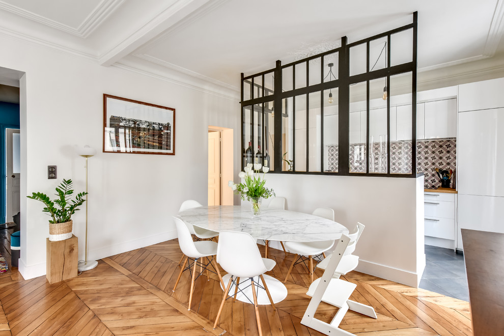Example of a danish medium tone wood floor and brown floor great room design in Paris with white walls