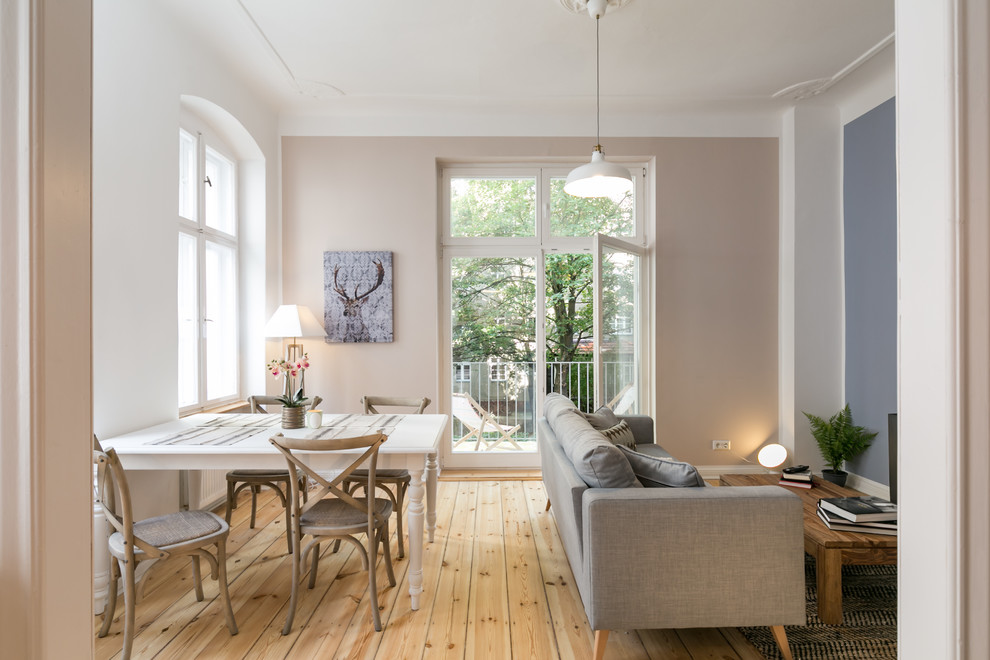 Inspiration for a mid-sized farmhouse medium tone wood floor and brown floor dining room remodel in Berlin with white walls and no fireplace