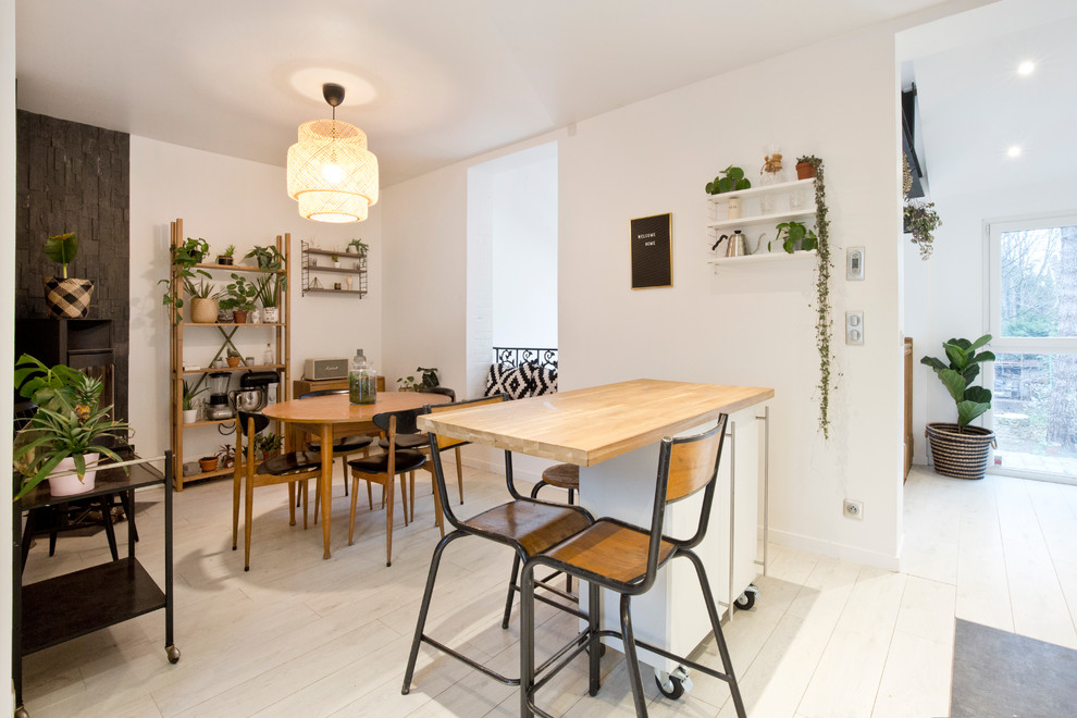 Great room - small scandinavian light wood floor great room idea in Paris with white walls and no fireplace