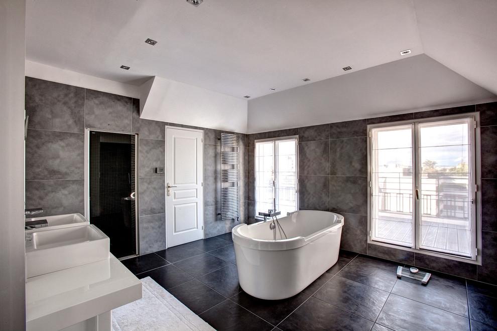 Ejemplo de cuarto de baño principal, contemporáneo, grande, con lavabo suspendido, bañera exenta, baldosas y/o azulejos grises, paredes grises, puertas de armario blancas y ducha empotrada
