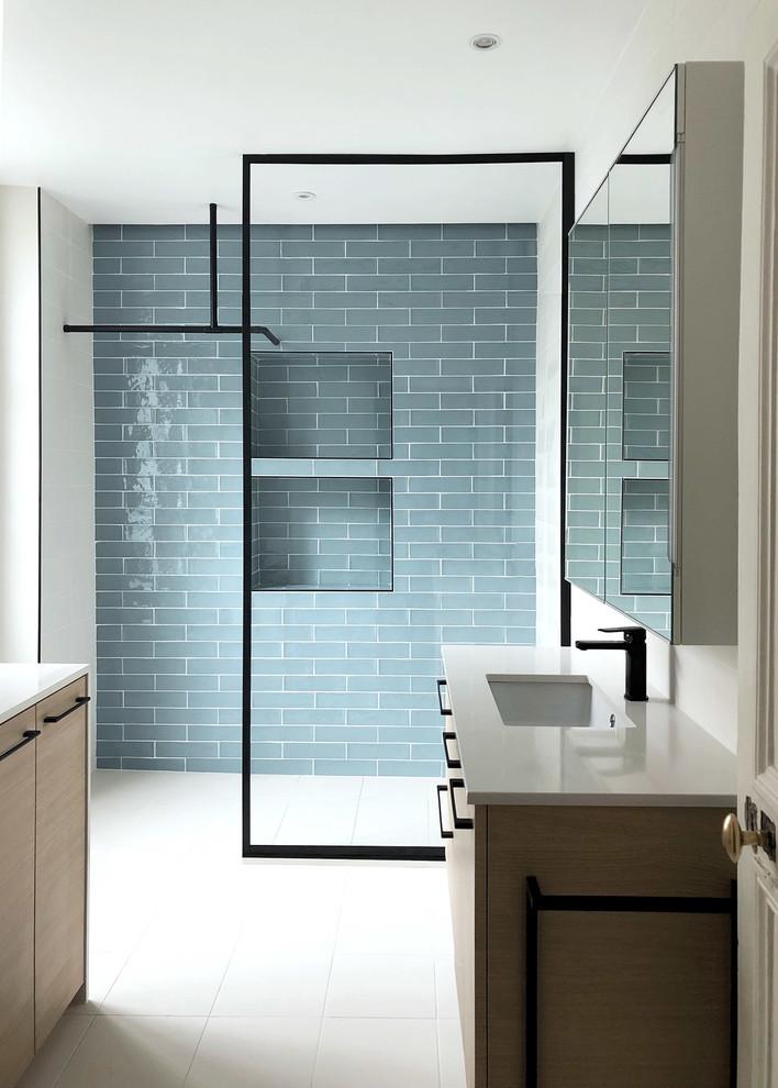 Réalisation d'une salle de bain principale design de taille moyenne avec un placard à porte affleurante, des portes de placard en bois clair, une douche à l'italienne, un carrelage bleu, des carreaux en allumettes, un mur blanc, un sol en carrelage de céramique, un plan vasque, un plan de toilette en quartz modifié, un sol blanc, un plan de toilette blanc, un WC séparé et aucune cabine.