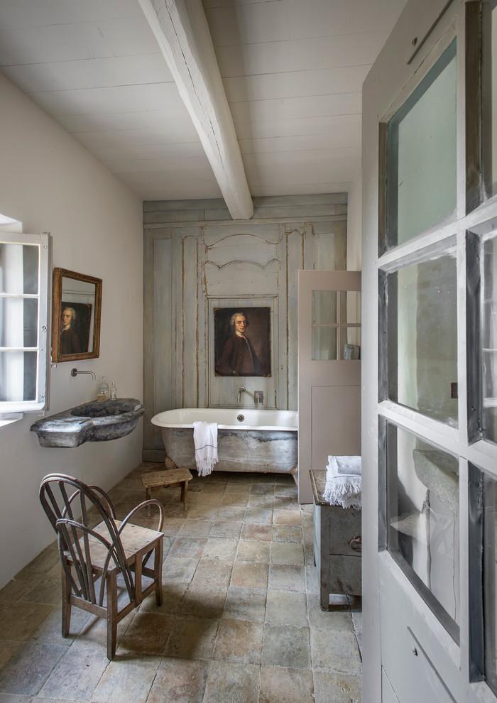 Idée de décoration pour une grande salle de bain principale champêtre avec un lavabo suspendu, une baignoire sur pieds, un mur blanc, des portes de placard en bois vieilli et un sol en carreau de terre cuite.