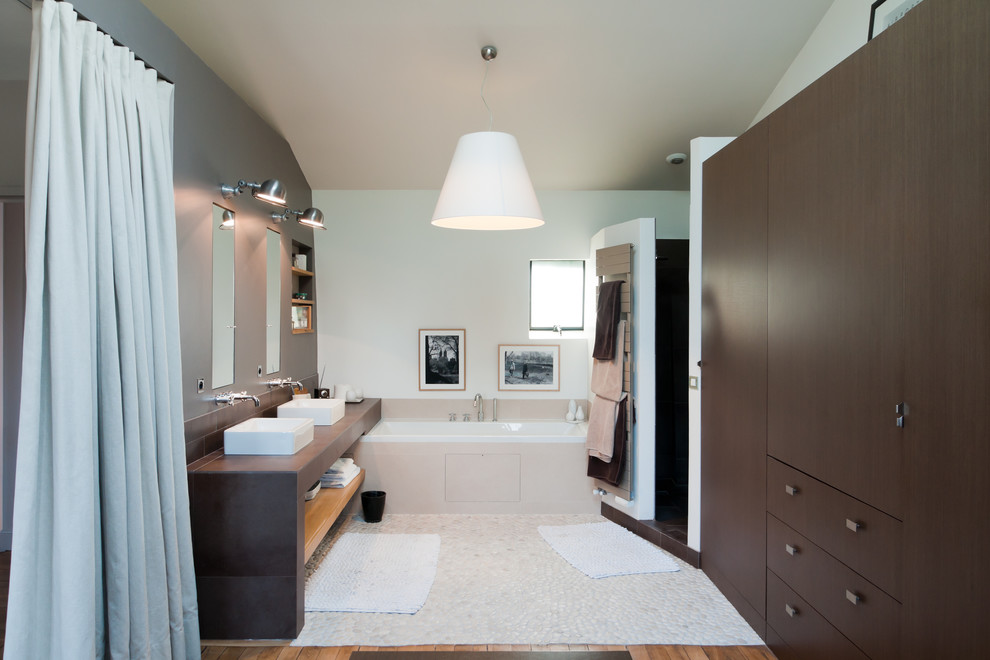 Bathroom - contemporary master pebble tile floor bathroom idea in Paris with a vessel sink, flat-panel cabinets, dark wood cabinets and white walls