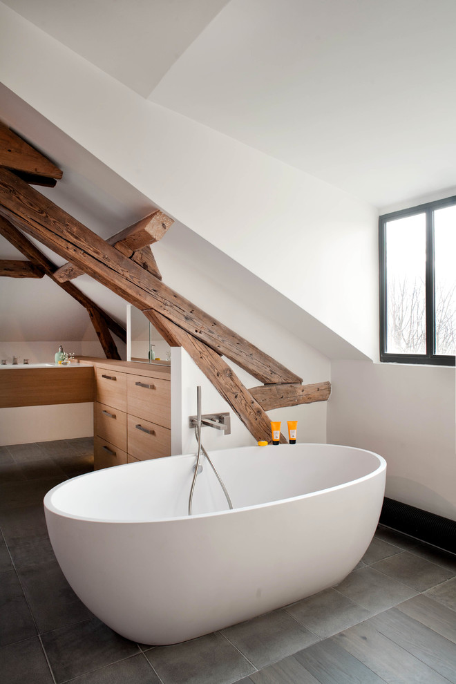 Trendy freestanding bathtub photo in Paris with flat-panel cabinets, medium tone wood cabinets and white walls